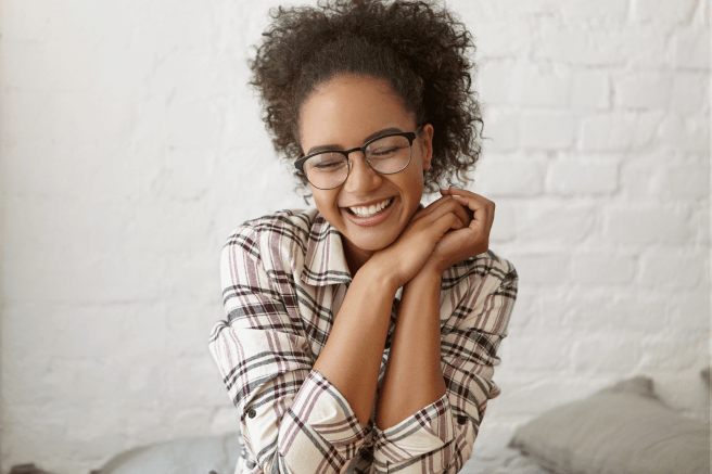 A young woman wearing glasses and smiling