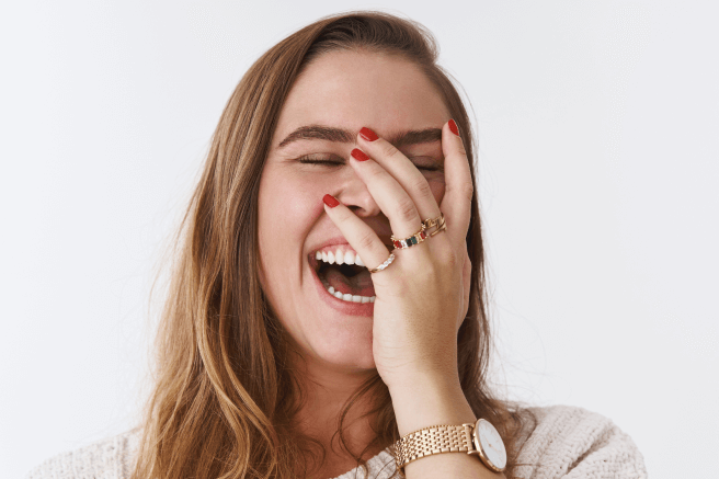 A young woman with her hand over face and laughing