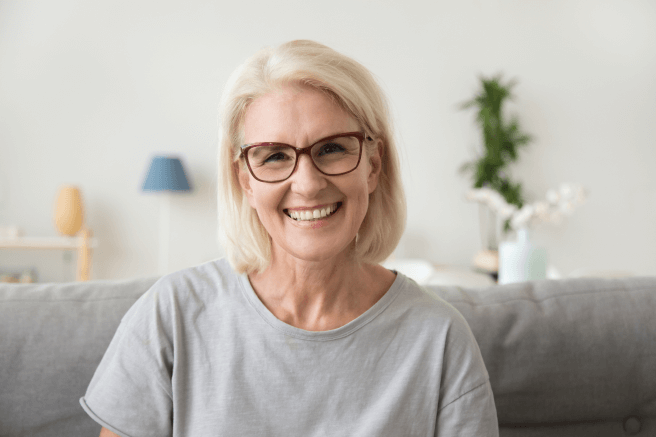 Older woman wearing glasses and sitting on a couch smiling