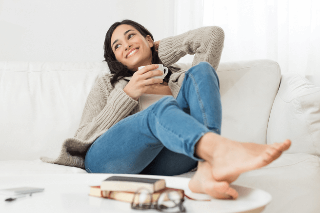 A woman relaxing on a couch with her feet on a coffee table