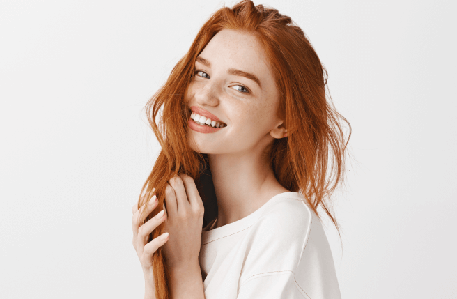 A beautiful young woman with red hair smiling
