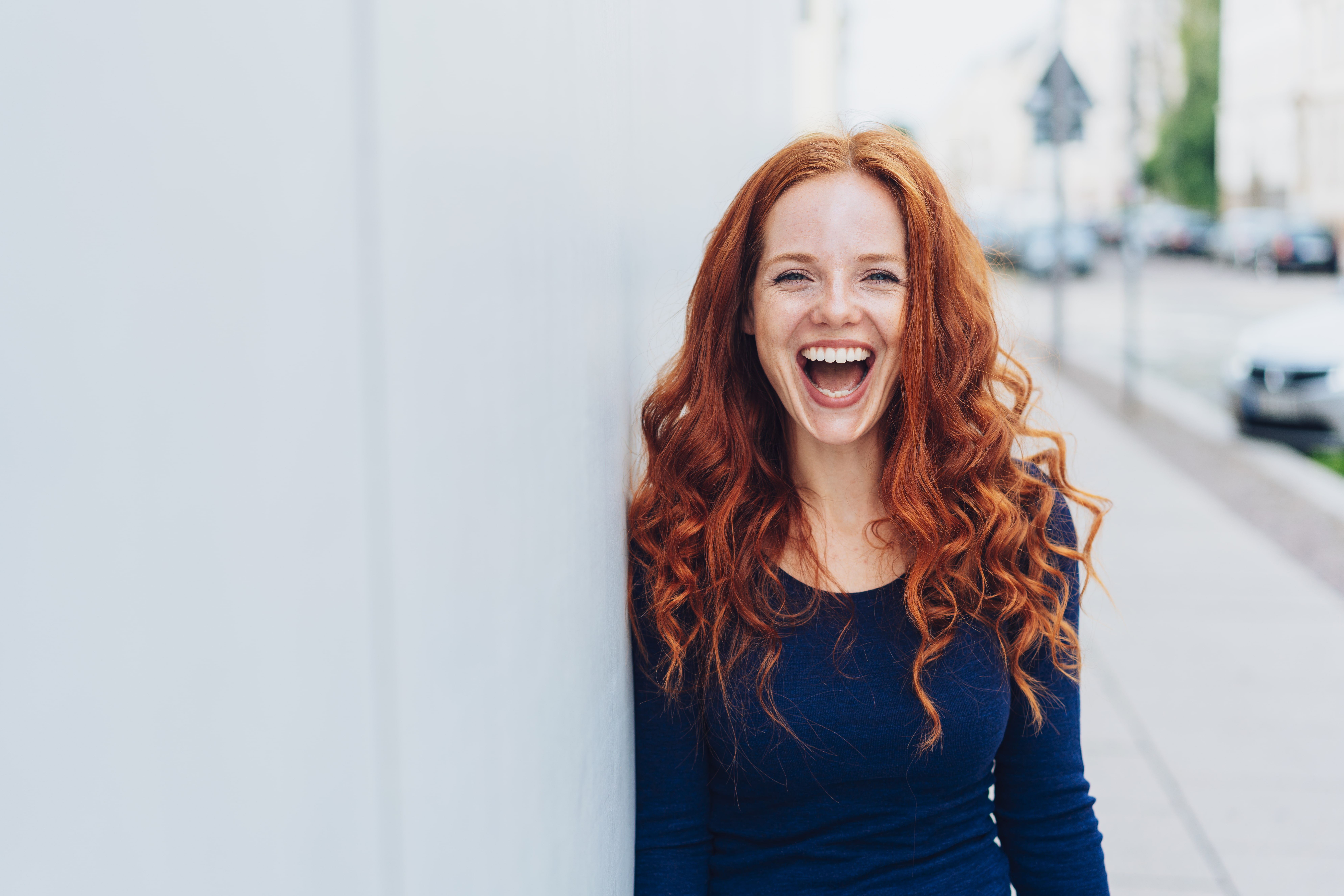 A woman with a wide open smile, curly red hair, and bright blue shirt leaning against a white wall with a city street in the background