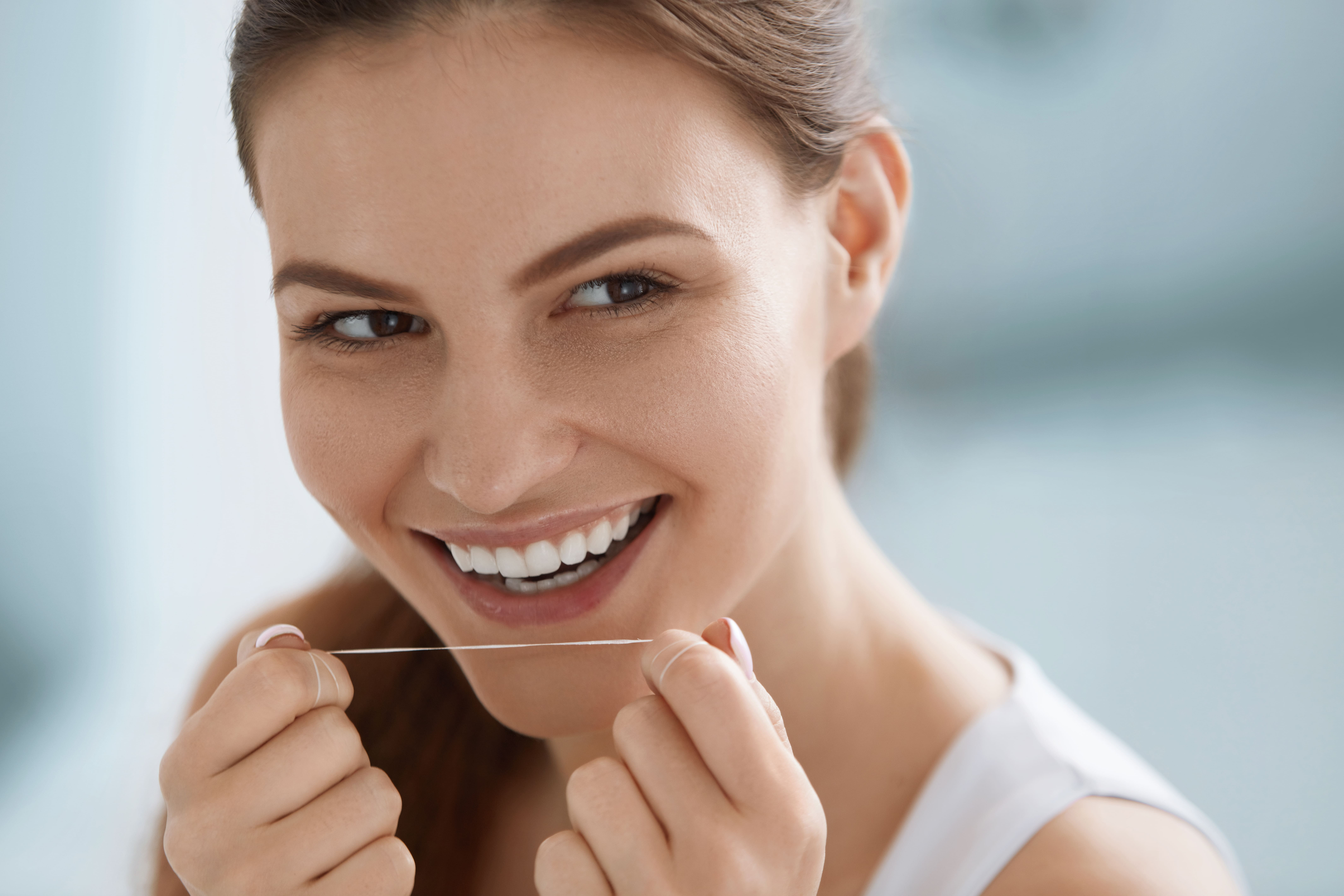 A smiling woman holding a string of floss, about to floss her teeth