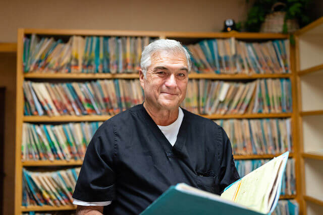 Dr. Goia looking at a patient's file in his dental office in Phoenix, AZ