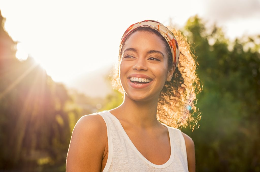 A smiling woman with dark curly hair pulled back in a headband, with the sun coming through the trees behind her