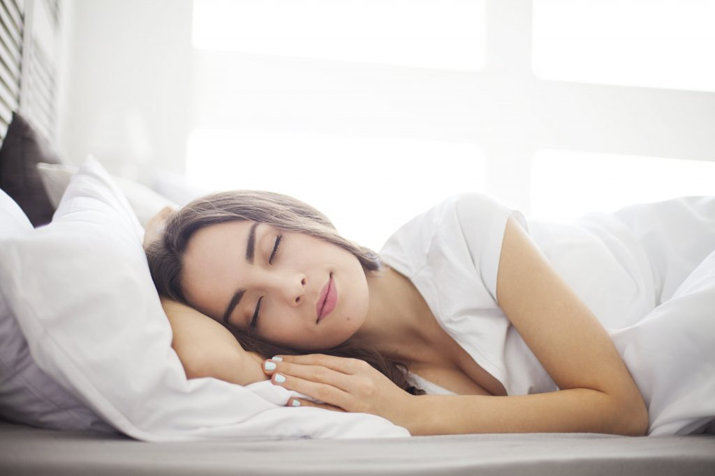 A woman with dark hair lying in bed asleep and smiling